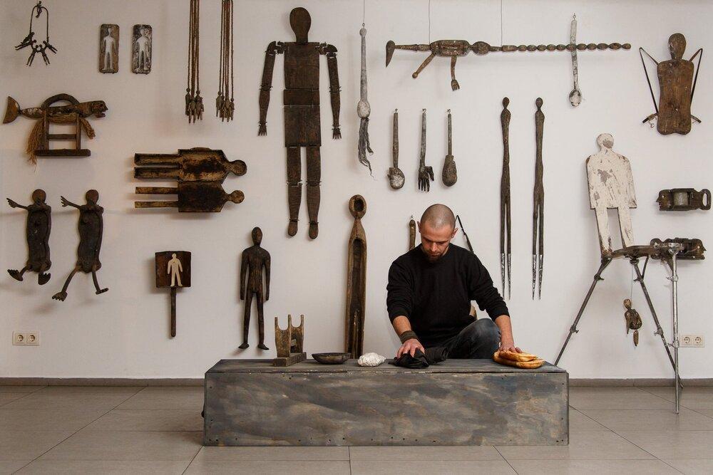 Константин Зоркин на фоне своих работ, выставка «Більше ніж скульптура», Art Ukraine Gallery, источник: альбом галереи об открытии выставки
