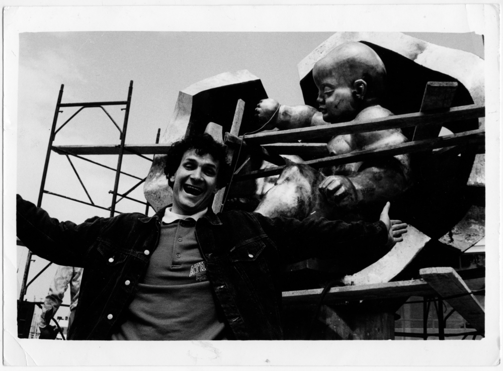Михаїл Рева на фоні пам'ятника Ернста Неізвєстного «Золоте дитя», 1995. Надано художником