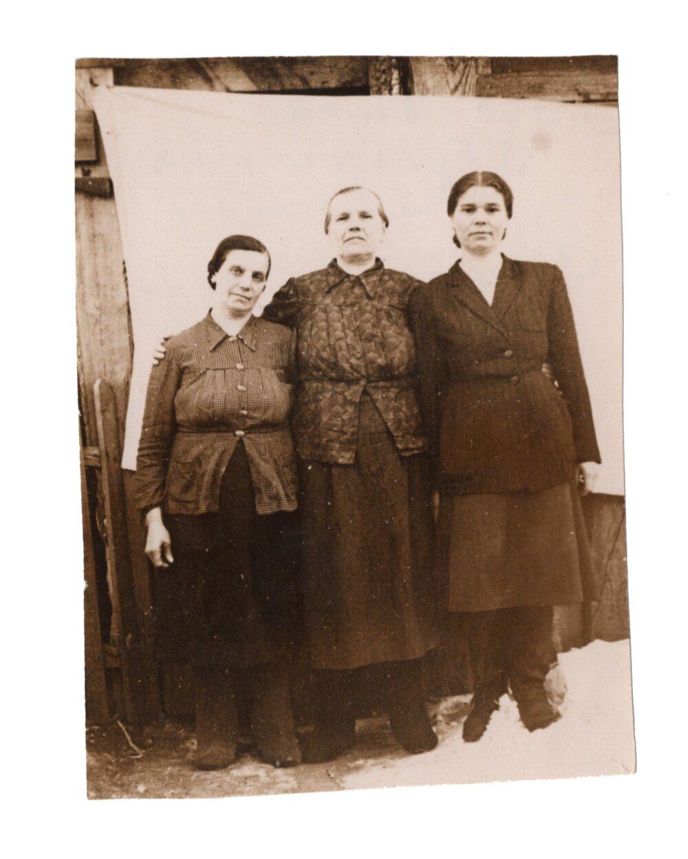 У центрі ― Катерина Слупська, ліворуч ― Іванна Кісь (сусідка), праворуч ― Текля Швидків (жінка, яка проводила християнські обряди замість священика), поселення Алгач, 1955. Джерело: Меморіальний музей «Територія Терору»