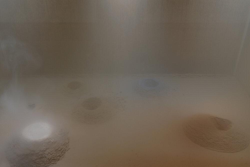 Дора Будор. Происхождение, 2019. Специальная экологическая камера (реактивная электронная система, компрессор, клапаны, 3D-печатные элементы, алюминий, акрил, светодиод, стекло, дерево, краска), органические и синтетические пигменты, диатомовая земля, пыль, войлок. 152 × 160 × 86 см