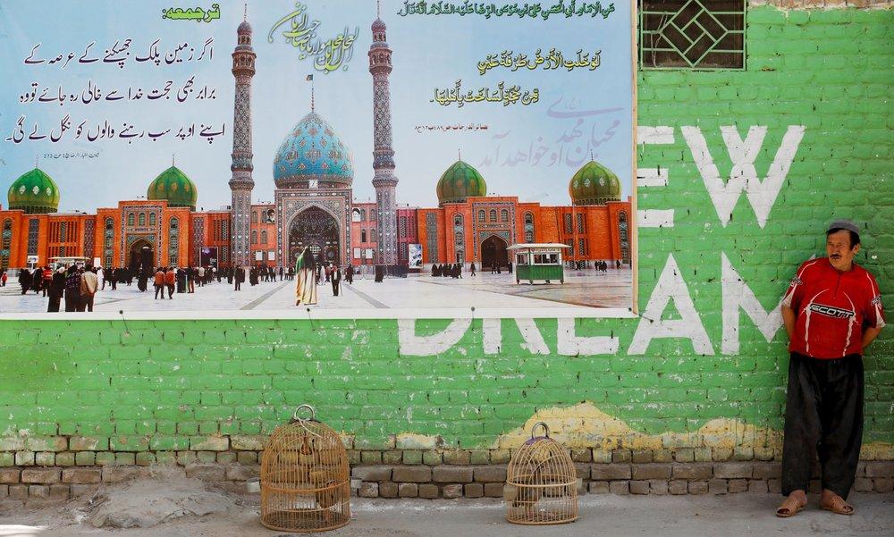 Чоловік з парою чукарів у клітках біля плаката із зображенням мечеті Джамкаран в Ірані