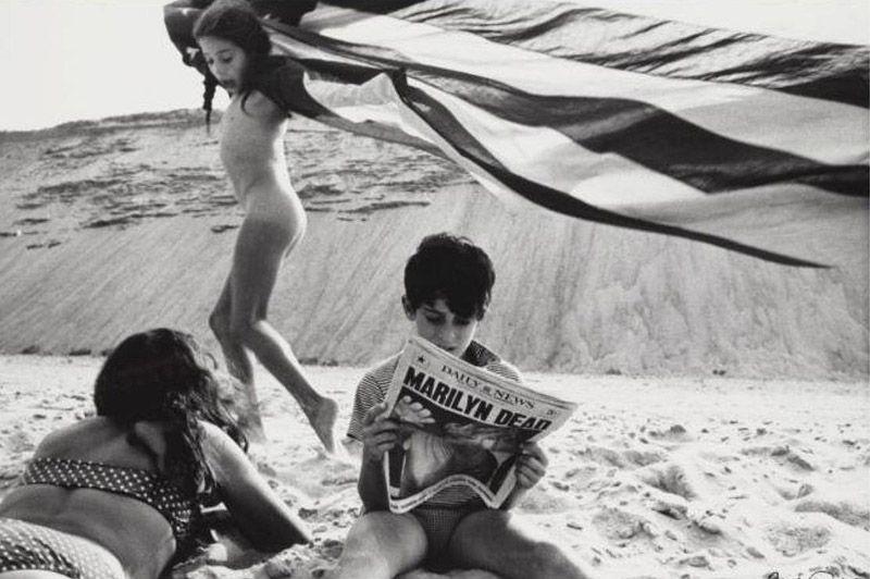 Хлопчик читає газету з заголовком «Мерилін мертва»