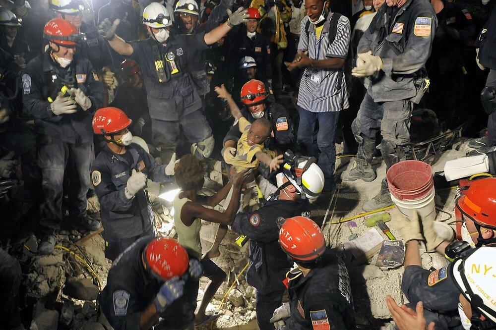 19 січня 2010 року, через сім днів після землетрусу в 7,0 балів у столиці Гаїті Порт-о-Пренс команда рятівників змогла підняти хлопчика Кікі з-під завалів. Світлина: Matthew McDermott/ Polaris/Eyevine