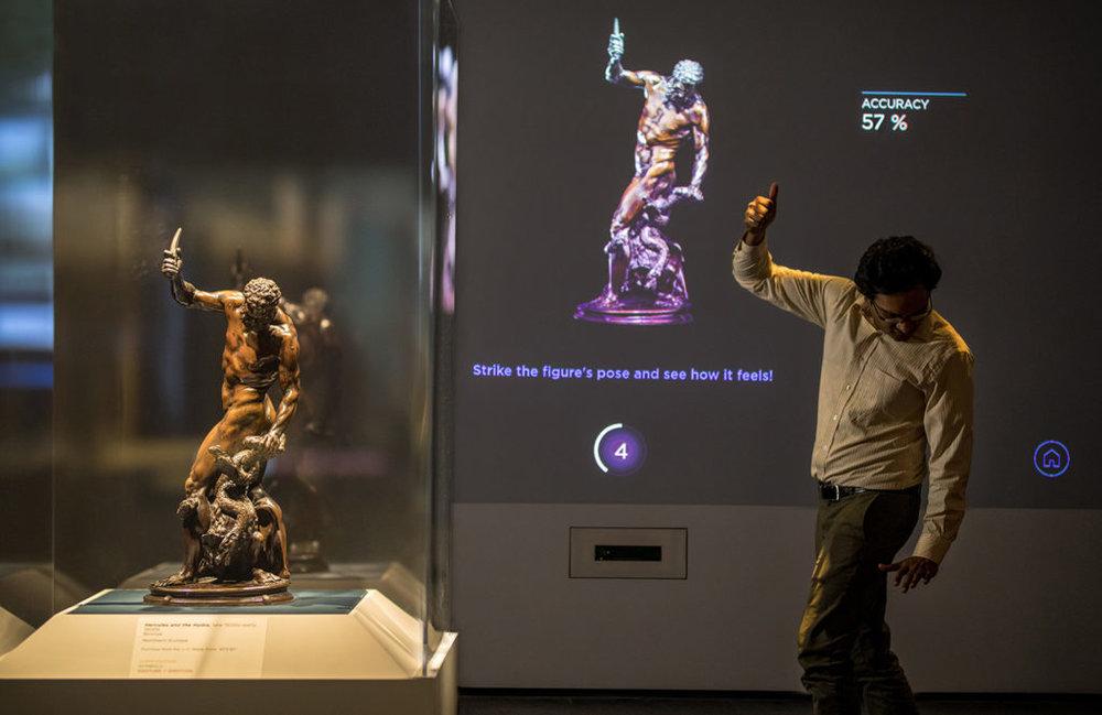 Відвідувач пробує відтворити позу скульптури